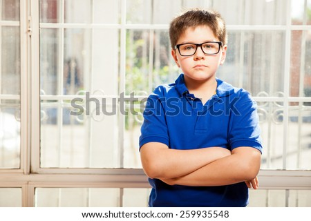 Portrait of a blond little boy with his arms crossed relaxing at home - stock photo