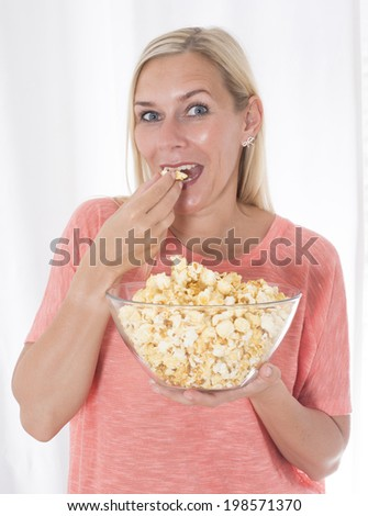 portrait of a blond woman eating popcorn