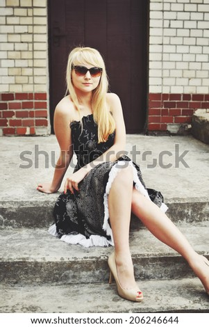 Portrait of a blond woman in black dress outdoor. Summertime.