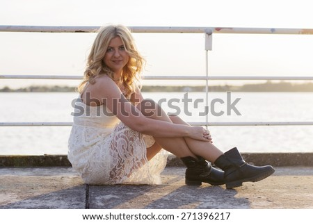 Portrait of a blond woman wearing white lace dress and short black boots with lake behind her enjoying sun.