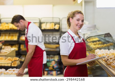 Portrait of a blonde baker with her colleague in bakery - stock photo