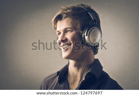 Portrait of a blonde guy listening to the music with headphones