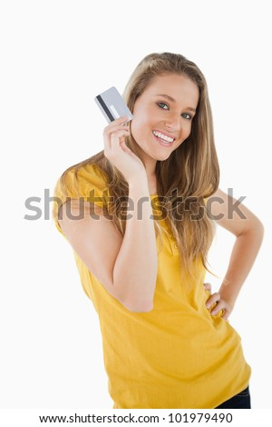 Portrait of a blonde student showing a credit card against white background - stock photo