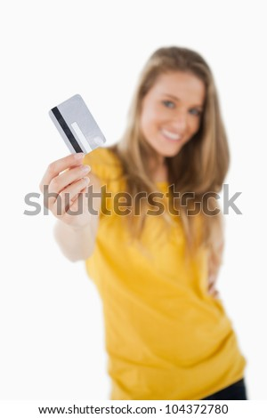 Portrait of a blonde student tending a credit card against white background