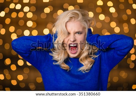 Portrait of a blonde woman covering her ears and screaming over holidays lights background - stock photo