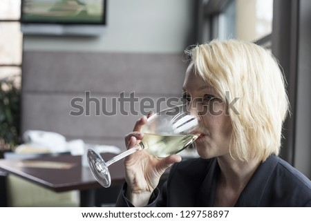 Portrait of a blonde woman drinking a glass of white wine.