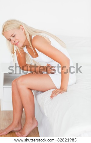 Portrait of a blonde woman having a stomachache in her bedroom - stock photo