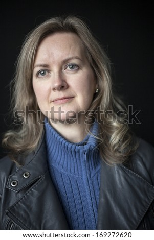Portrait of a blonde woman on a black background. - stock photo