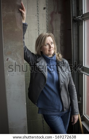 Portrait of a blonde woman on in a warehouse. - stock photo