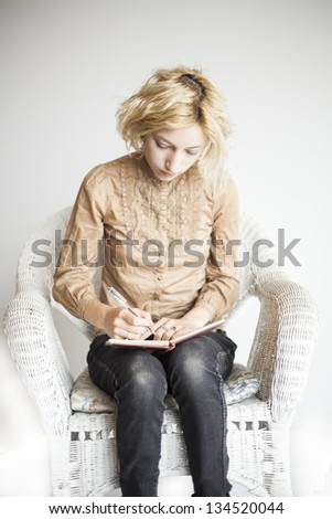 Portrait of a blonde woman with blue eyes writing in her journal. - stock photo