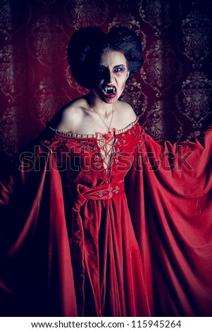 Portrait of a bloodthirsty female vampire over red vintage background. - stock photo