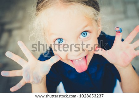 portrait of a blue eyed girl with her tongue out