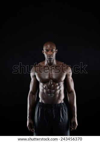 Portrait of a bodybuilder with muscular physique posing against black background. Masculine african fitness model standing shirtless. - stock photo