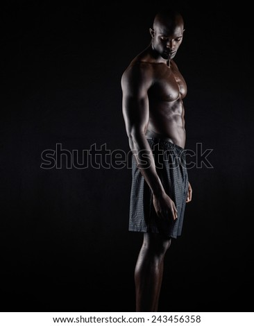 Portrait of a bodybuilder with muscular physique standing against black background. Masculine african fitness model standing shirtless looking down. - stock photo
