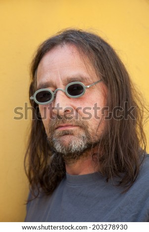 Portrait of a Bohemian middle-aged man with shoulder-length hair and fancy small round sunglasses with metallic frame, on yellow