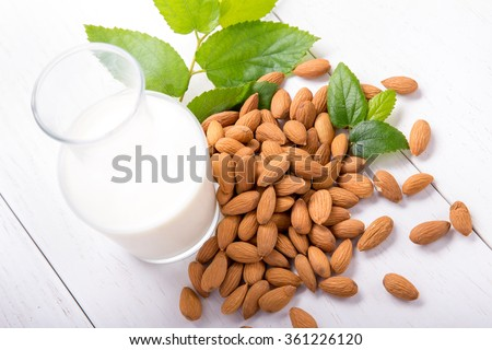 portrait of a bottle of fresh almond milk with a pile of almond on white background - stock photo