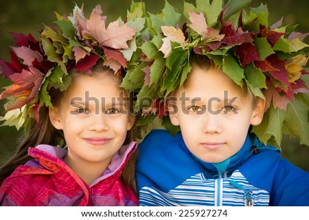 Portrait of a boy and a girl wearing wreathes of fall leaves - stock photo