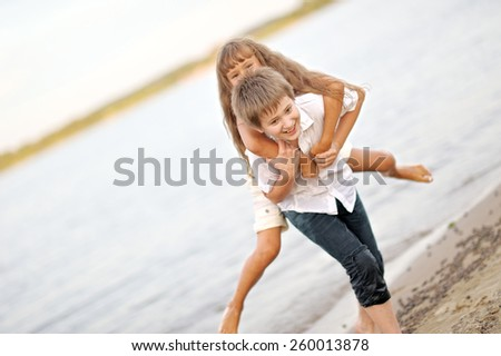 Portrait of a boy and girl playing on the beach - stock photo