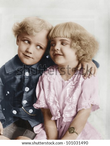 Portrait of a boy and girl with arm around her - stock photo