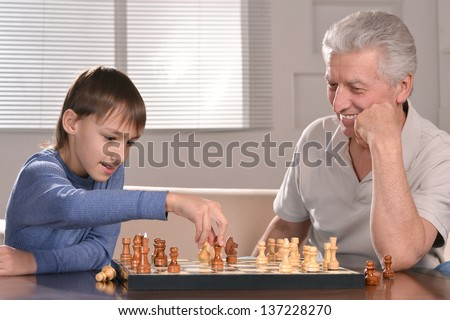portrait of a boy and grandfather playing chess at home - stock photo