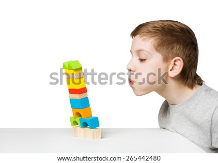 Portrait of a boy blowing on falling house made of wooden blocks - stock photo