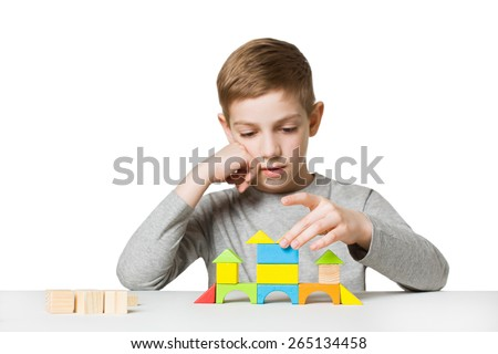 Portrait of a boy building house made of wooden blocks - stock photo