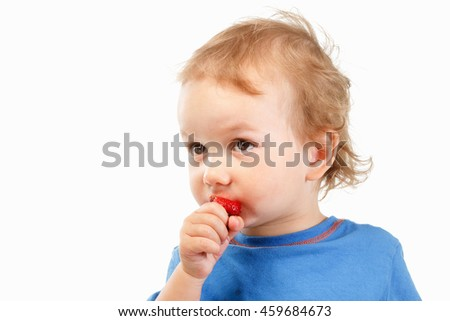 Portrait of a boy eating strawberries, shot in studio on white background