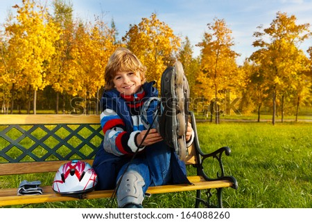 Portrait of a boy getting ready for skating sitting on the bench in the autumn park - stock photo