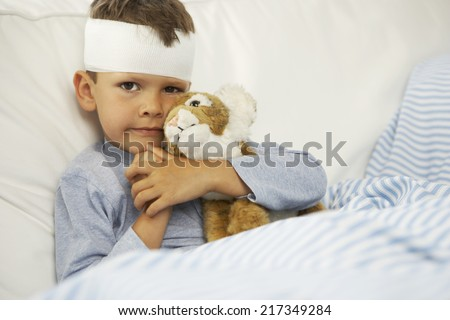 Portrait of a boy hugging a stuffed toy with a bandage on his forehead - stock photo