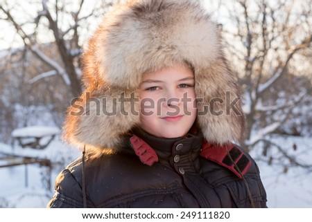 Portrait of a boy in a fur hat in winter - stock photo