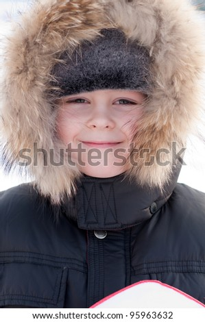 Portrait of a boy in a jacket with fur