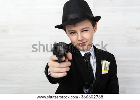 Portrait of a Boy in a suit with a gun! Gangster! - stock photo