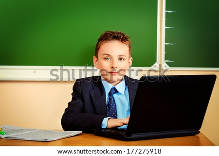Portrait of a boy in a suit working on a laptop at school. Education. - stock photo