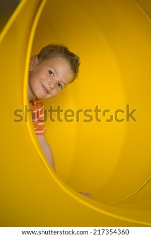 Portrait of a boy in a tubular slide and grinning - stock photo