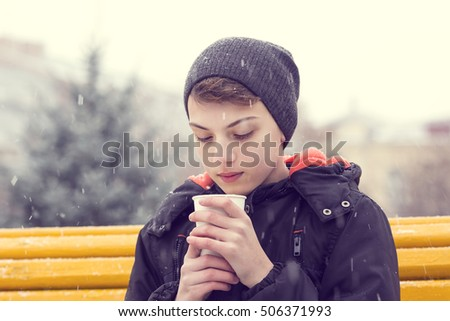 Portrait of a boy in a winter park with a paper cup of cappuccino