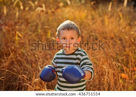 Portrait of a boy in boxing gloves - stock photo