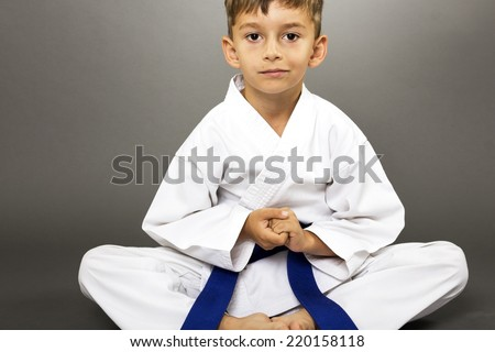 Portrait of a boy in kimono training on the floor isolated over gray background  - stock photo
