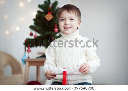 Portrait of a boy in white sweater on the Christmas tree.  - stock photo