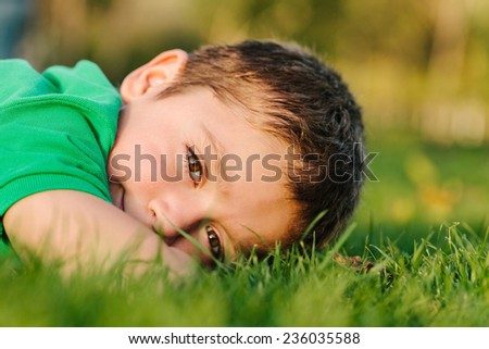 Portrait of a Boy Laying on Grass - stock photo