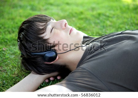 Portrait of a boy listening to music with headphones laid on the grass - stock photo