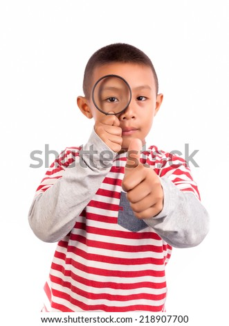 Portrait of a boy looking through the magnifying glass - stock photo