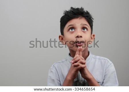 Portrait of a boy looks up and thinks deep - stock photo