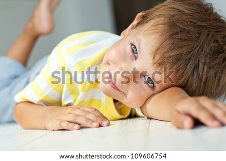 Portrait of a boy lying on the floor of the house - stock photo
