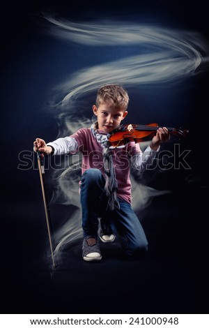 Portrait of a boy posing with his violin. over black background.