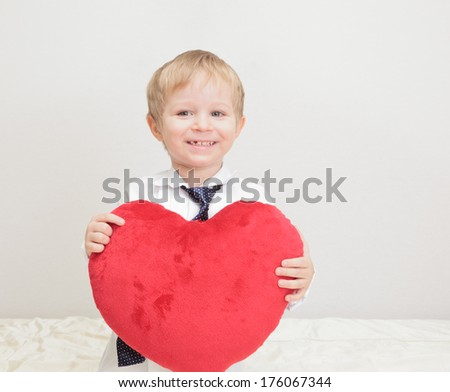 portrait of a boy presenting heart shaped pillow - stock photo