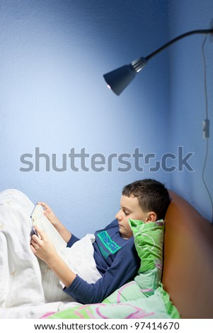 Portrait of a boy reading a book at bedtime, lying in his bed - stock photo