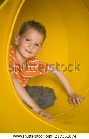 Portrait of a boy sitting in a tubular slide and grinning - stock photo