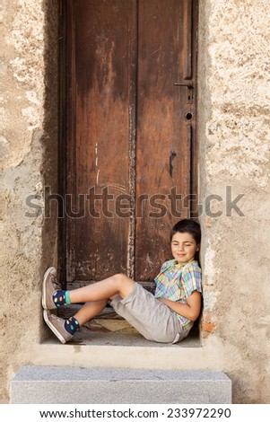 portrait of a boy sitting on the stairs of an old house