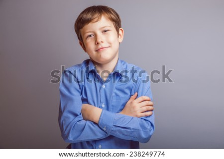 Portrait of a boy smiling brown hair European appearance on a gray background - stock photo