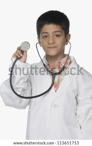 Portrait of a boy wearing lab coat and showing a stethoscope